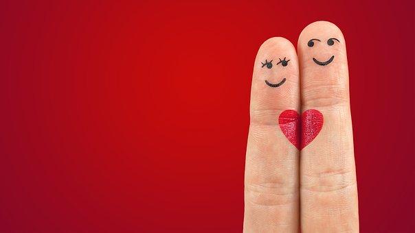 Deux doigts collés ensemble avec un coeur rouge au centre.